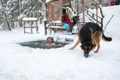 妇女在冰的孔游泳在一个冬天 免版税库存照片