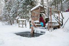 妇女在冰的孔游泳在一个冬天 图库摄影