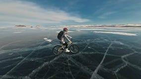 妇女在冰骑自行车 女孩在一件银色下来夹克、循环的背包和盔甲打扮 冰  股票视频