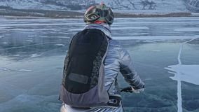 妇女在冰骑自行车 女孩在一件银色下来夹克、循环的背包和盔甲打扮 冰  影视素材