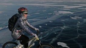 妇女在冰骑自行车 女孩在一件银色下来夹克、循环的背包和盔甲打扮 射击 影视素材