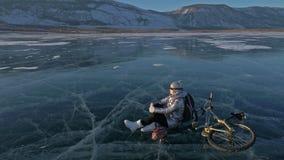 妇女在冰骑自行车 女孩在一件银色下来夹克、循环的背包和盔甲打扮 的treadled 股票录像