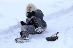 妇女在冷漠的路滑倒了,跌倒了并且伤害了自己 免版税库存照片
