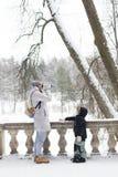 妇女在冷的wi的雪冬天喝咖啡热奶咖啡外面 免版税图库摄影
