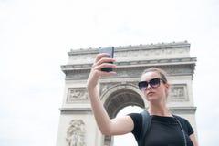 妇女在凯旋门做与电话的selfie在巴黎,法国 有智能手机的妇女在曲拱纪念碑 假期和观光 免版税库存图片