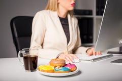 妇女在办公室用咖啡和油炸圈饼 库存照片