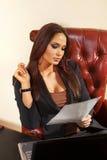 妇女在办公室读文件 免版税库存照片