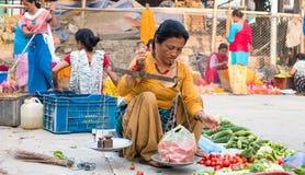 妇女在加德满都街市上卖了新鲜蔬菜 库存图片