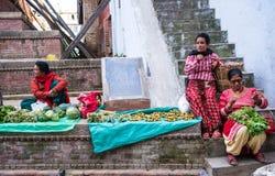 妇女在加德满都街市上卖了新鲜蔬菜 免版税库存照片