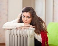 妇女在加热器附近温暖 库存图片