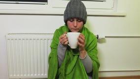 妇女在加热的幅射器和饮料茶附近温暖 股票录像