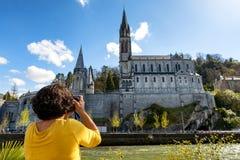 妇女在卢尔德,法国拍摄大教堂 库存图片
