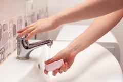 妇女在卫生间里采取肥皂并且打开水龙头洗她的在一个白色水槽的手 免版税库存图片
