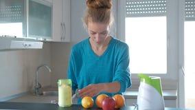 妇女在厨房在一台小搅拌器做果子圆滑的人 股票视频
