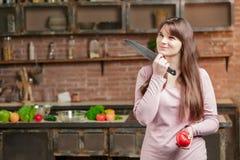 妇女在厨房里站立在与新鲜蔬菜的桌附近 女孩拿着一把刀子和一个蕃茄在她的手上 免版税图库摄影