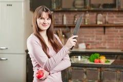 妇女在厨房里站立在与新鲜蔬菜的桌附近 女孩拿着一把刀子和一个蕃茄在她的手上 库存图片