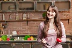 妇女在厨房里站立在与新鲜蔬菜的桌附近 女孩拿着一把刀子和一个蕃茄在她的手上 库存照片