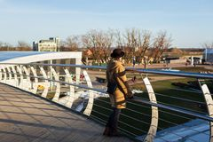 妇女在叶尔加瓦,拉脱维亚享受从Mitavas桥梁的看法在河Driksa 库存照片