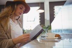 妇女在咖啡馆的读书菜单 库存图片