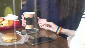 妇女在咖啡馆的` s手使用有LGBT镯子的一个电话关闭  股票视频