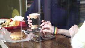 妇女在咖啡馆的` s手使用有LGBT镯子的一个电话 影视素材