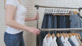 妇女在商店移动与衣裳的棚架 影视素材