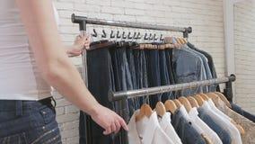 妇女在商店移动与衣裳的棚架 股票视频