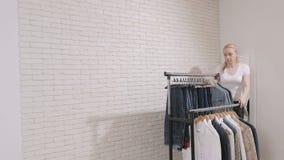 妇女在商店移动与衣裳的棚架 股票录像