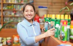 妇女在商店选择农业化学 免版税库存照片