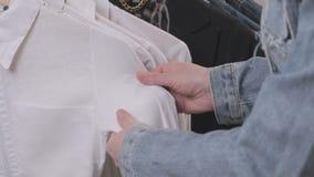 妇女在商店选择垂悬在一个挂衣架的衣裳 影视素材