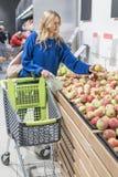 妇女在商店选择苹果 免版税库存照片