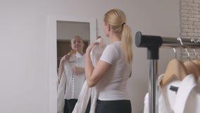 妇女在商店选择衣裳,在镜子前面敬佩 股票录像
