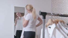 妇女在商店选择衣裳,在镜子前面敬佩 影视素材
