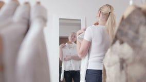 妇女在商店选择衣裳,在镜子前面敬佩 股票视频