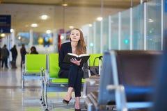妇女在国际机场终端,阅读书 库存图片