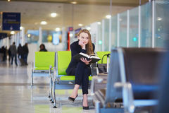 妇女在国际机场终端,阅读书 免版税库存照片