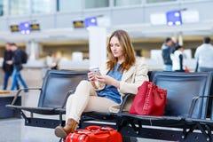 妇女在国际机场,读ebook 免版税库存照片