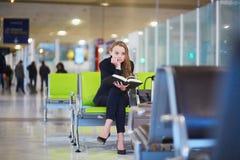 妇女在国际机场终端,阅读书 免版税库存图片