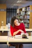 妇女在图书馆发现某事非常有趣 免版税库存照片