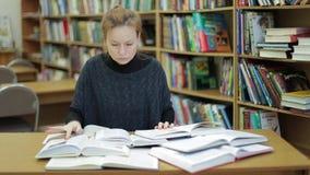 妇女在图书馆读很多书 她由相当数量信息害怕 我太多不会做它学习 股票视频