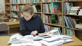 妇女在图书馆读很多书 她由相当数量信息害怕 我太多不会做它学习 影视素材