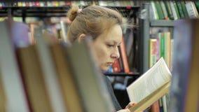 妇女在图书馆里读一本书 她是在书之间的走廊 股票录像