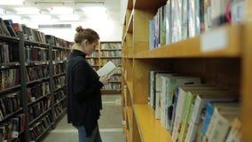 妇女在图书馆里读一本书 她是在书之间的走廊 影视素材