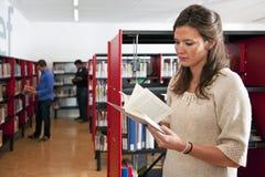 妇女在图书馆里 免版税库存图片