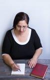 妇女在土气样式的一张木桌上 免版税图库摄影