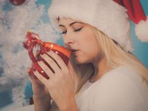 妇女在圣诞老人圣诞节帽子饮用的茶或咖啡 库存照片