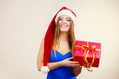 妇女在圣诞老人帽子拿着礼物盒 背景圣诞节关闭红色时间 免版税库存图片