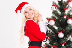 妇女在圣诞老人服装和帽子在圣诞树附近 免版税库存图片