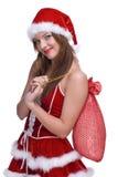 妇女在圣诞老人礼服和礼品袋子 免版税库存照片