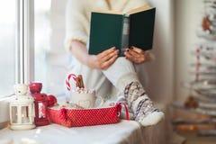 妇女在圣诞节的阅读书装饰了得在家 库存图片